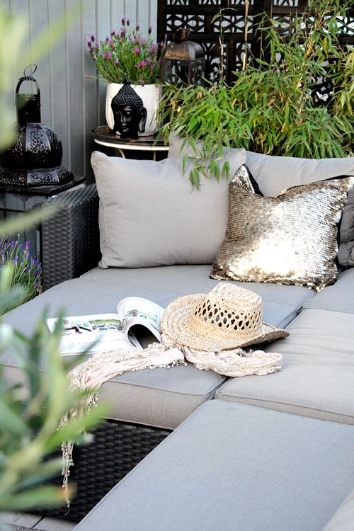 Outdoor couch with cushions and surrounded by plants