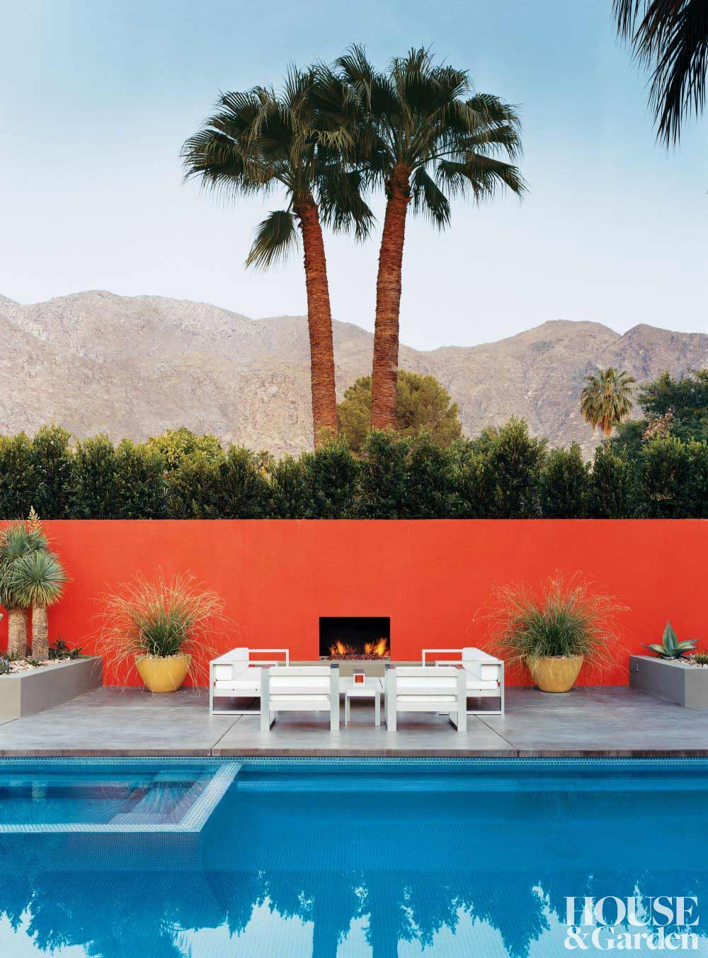 White outdoor setting by pool with red fence.