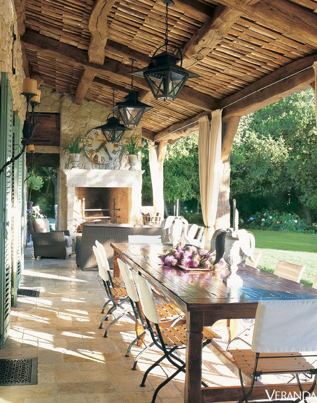 mediterranean veranda with dining table and open fireplace